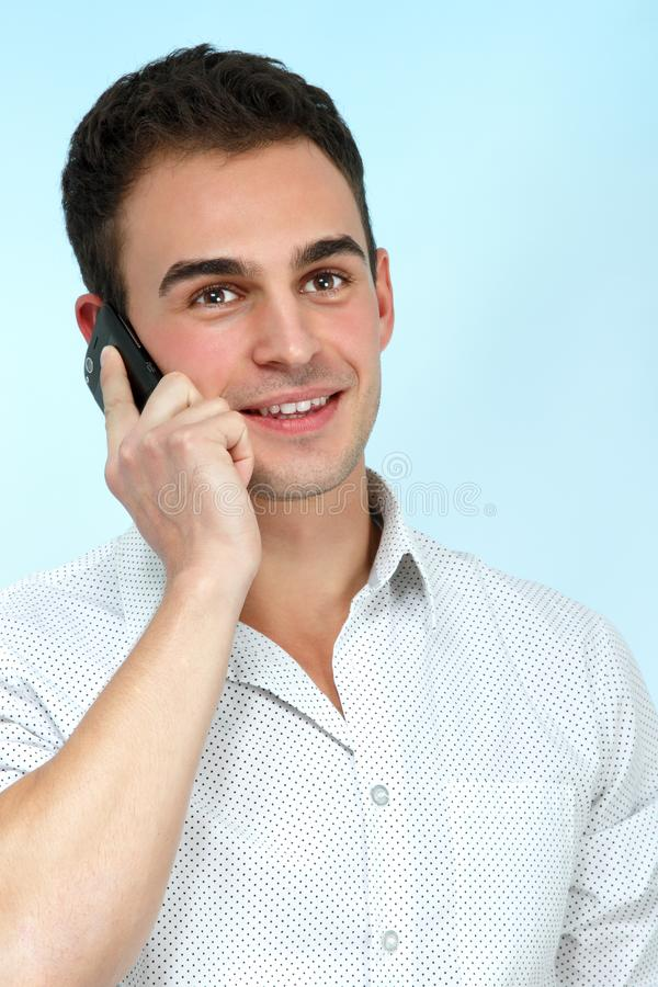Giovane sorridente che gode di una conversazione con il cellulare sopra il bl fotografie stock