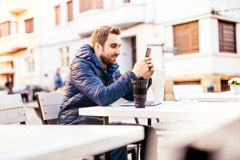 Giovane sorridente che lavora dall'ufficio all'aperto Rivestimento d'uso dell'uomo che invia i messaggi sullo smartphone mentre a fotografie stock libere da diritti