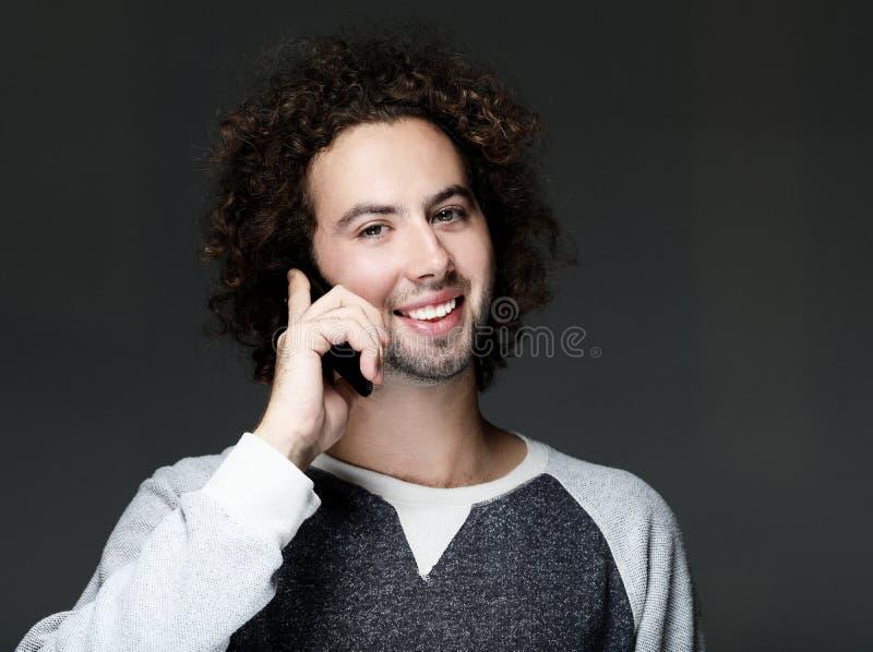 Giovane sorridente che parla lo smartphone ed esaminando la macchina fotografica immagine stock