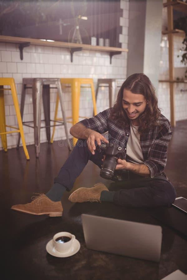 Giovane sorridente che usando la macchina fotografica di DSLR mentre sedendosi con il computer portatile sul pavimento immagine stock
