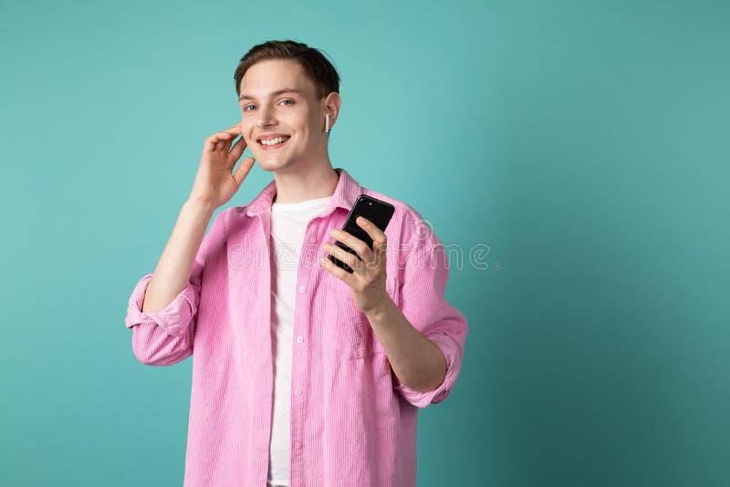 Giovane sorridente felice in camicia rosa che parla sul telefono cellulare facendo uso delle cuffie senza fili fotografia stock libera da diritti