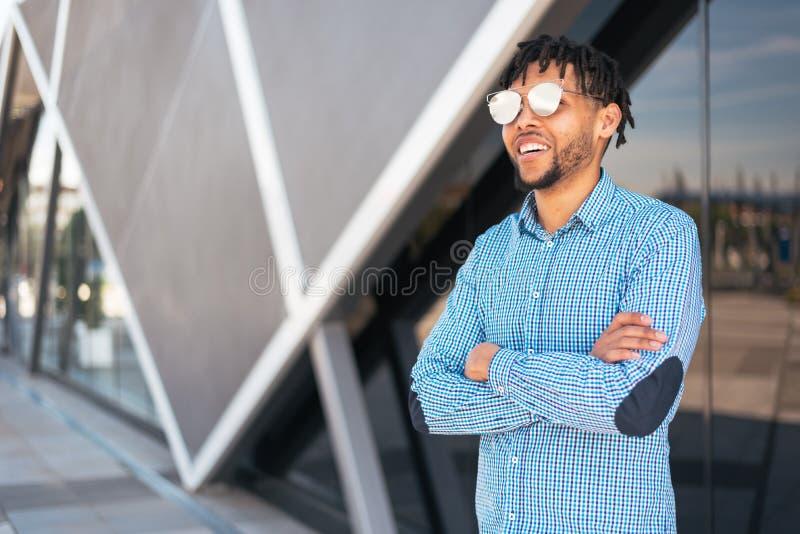 Giovane sorridere americano dell'uomo soddisfatto del ritratto degli occhiali da sole all'aperto fotografia stock libera da diritti