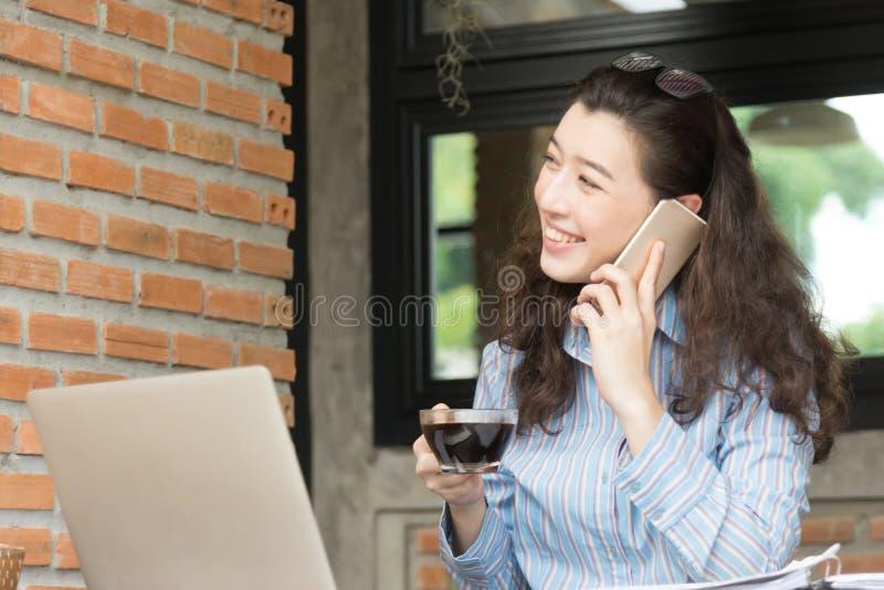 Giovane sorriso allegro della donna di affari che si siede al caff? del terrazzo, godente della comunicazione online facendo uso  fotografia stock libera da diritti