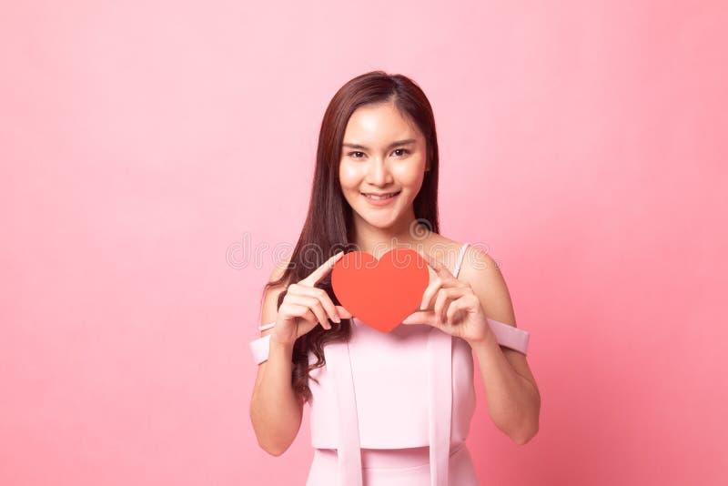 Giovane sorriso asiatico della donna con cuore colto fotografie stock libere da diritti