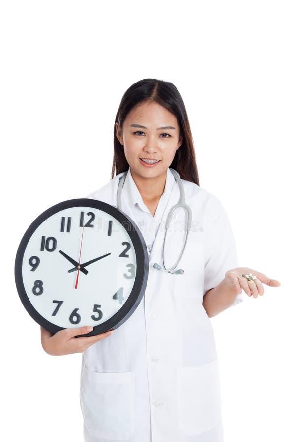 Giovane sorriso femminile asiatico di medico con un orologio e le pillole a disposizione fotografie stock libere da diritti
