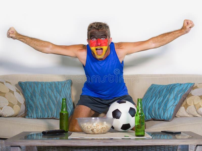 Giovane sostenitore attraente di calcio dell'uomo con la partita di sorveglianza felice ed emozionante del fronte dipinta bandier fotografia stock libera da diritti