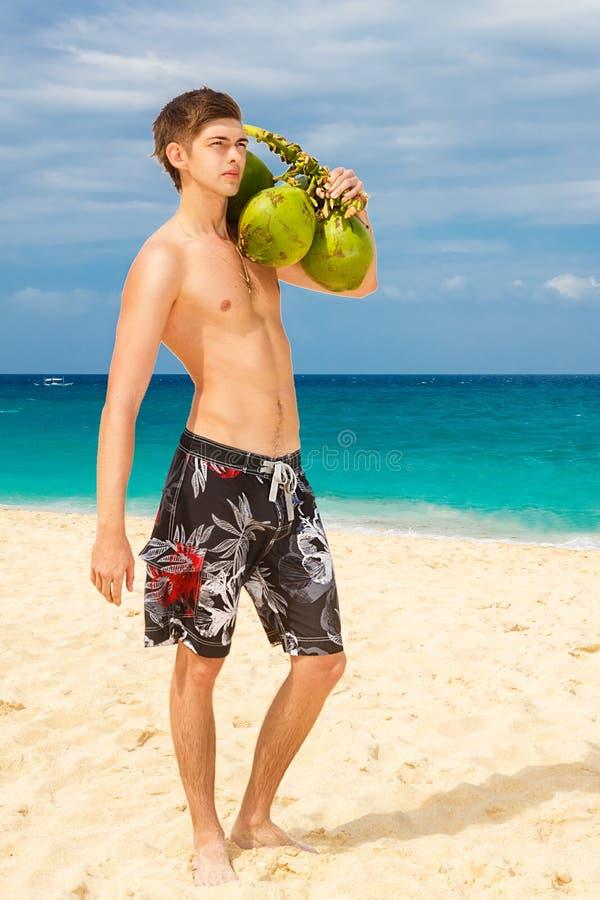 Giovane spiaggia maschio bella felice che sorride al coconu della tenuta della macchina fotografica fotografia stock libera da diritti