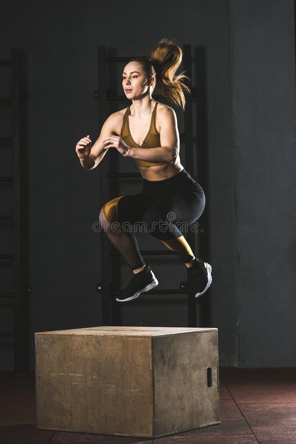 Giovane sportiva che salta sul blocco di legno fotografie stock