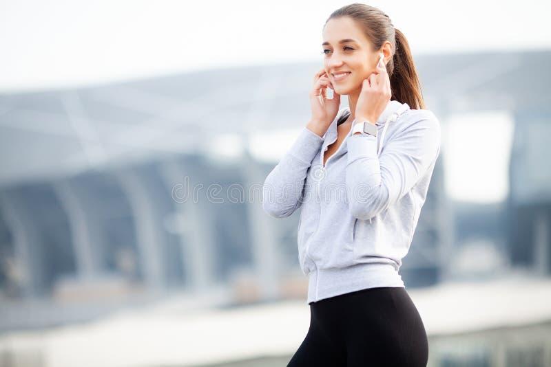 Giovane sportiva graziosa che mette sulle cuffie e che ascolta la musica nella città immagine stock libera da diritti