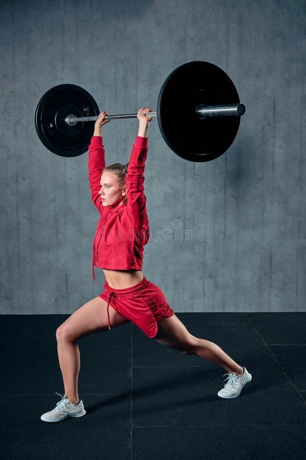 Giovane sportiva sforzata pronta a esercitarsi della stampa della spalla con il bilanciere pesante immagine stock