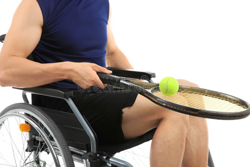 Giovane sportivo con la racchetta di tennis e palla che si siede in sedia a rotelle sul fondo bianco immagine stock libera da diritti