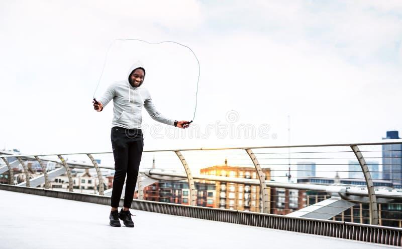 Giovane sportivo nero attivo che salta con una corda in una città, maglia con cappuccio d'uso immagini stock libere da diritti