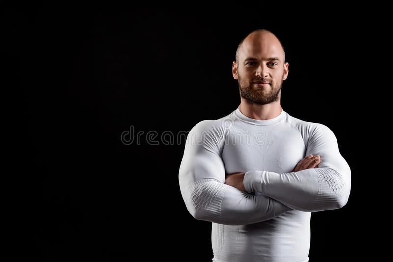 Giovane sportivo potente in abbigliamento bianco sopra fondo nero fotografie stock libere da diritti