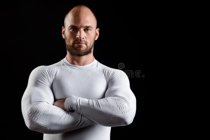 Giovane sportivo potente in abbigliamento bianco sopra fondo nero fotografia stock