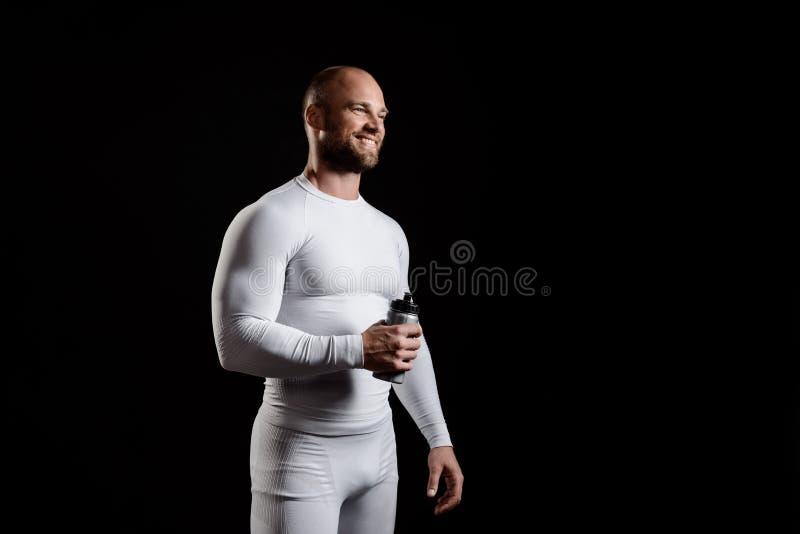Giovane sportivo potente in abbigliamento bianco sopra fondo nero immagini stock libere da diritti