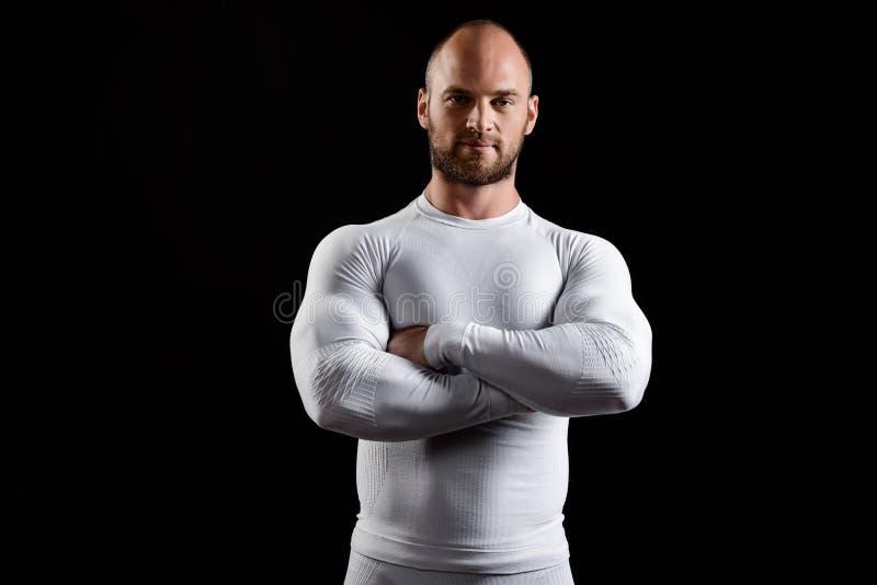 Giovane sportivo potente in abbigliamento bianco sopra fondo nero fotografie stock