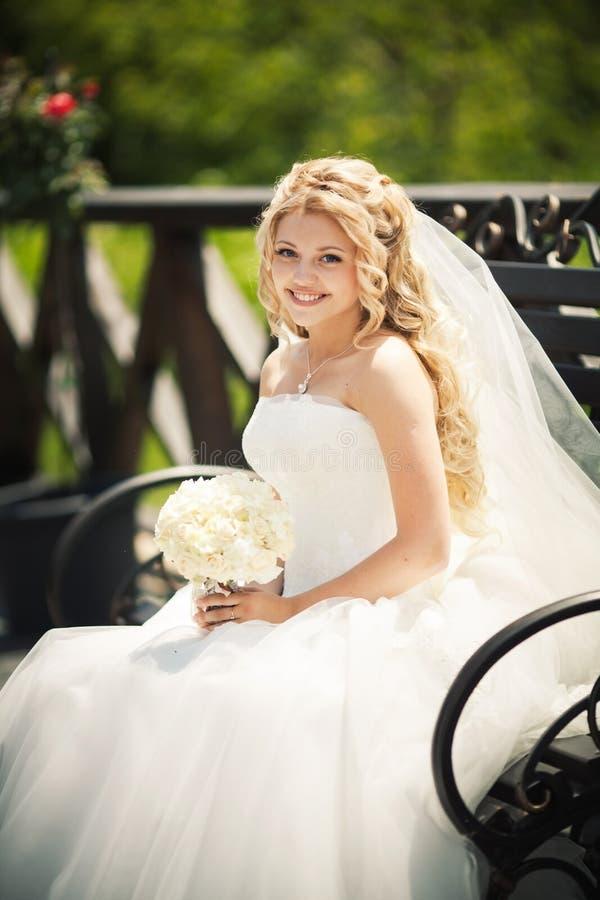 Giovane sposa attraente che si siede con il mazzo immagine stock libera da diritti