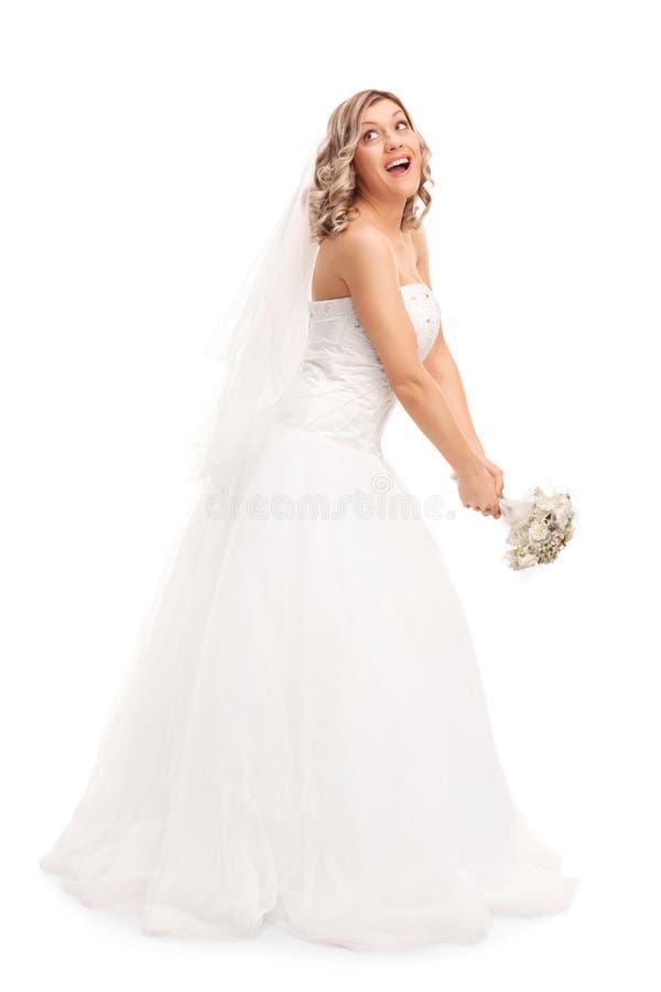Giovane sposa che lancia il suo mazzo di nozze fotografia stock libera da diritti