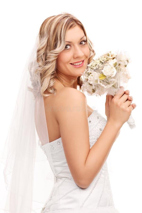Giovane sposa che tiene le nozze dei fiori fotografie stock libere da diritti