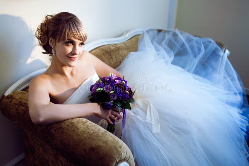 Giovane sposa con il fiore sul sofà fotografie stock