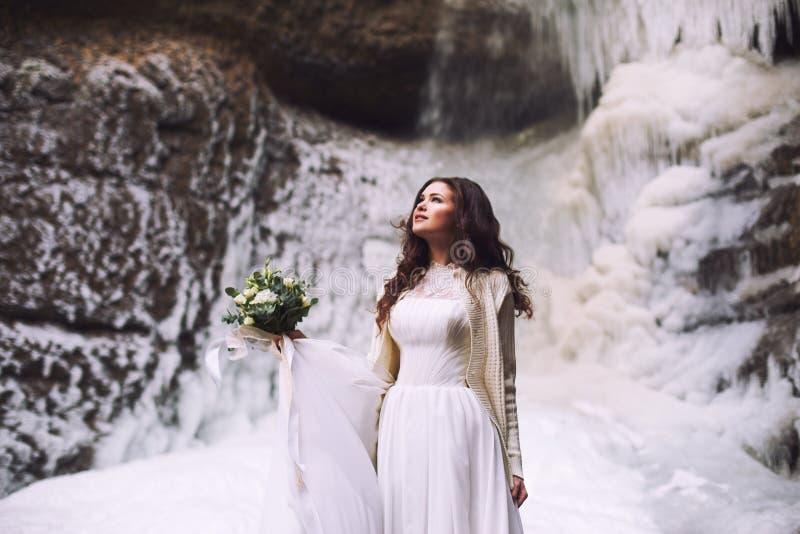 Giovane sposa con un mazzo dei fiori e di un vestito da sposa su un fondo di un ghiacciaio nelle montagne fotografia stock libera da diritti