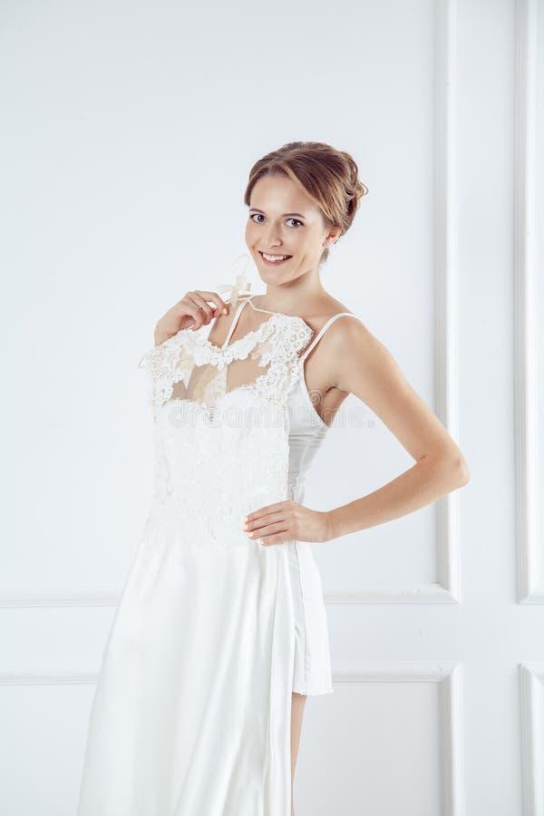 Giovane sposa nella stanza bianca che tiene vestito da sposa elegante immagine stock