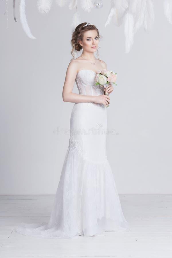 Giovane sposa vaga e bella in un vestito da sposa lussuoso dal pizzo immagini stock libere da diritti