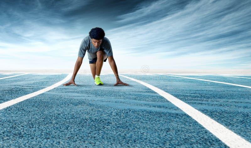 Giovane sprinter risoluto che prepara iniziare sull'eseguire pista fotografia stock libera da diritti