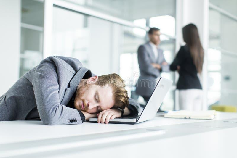 Giovane stanco che dorme nell'ufficio immagine stock libera da diritti