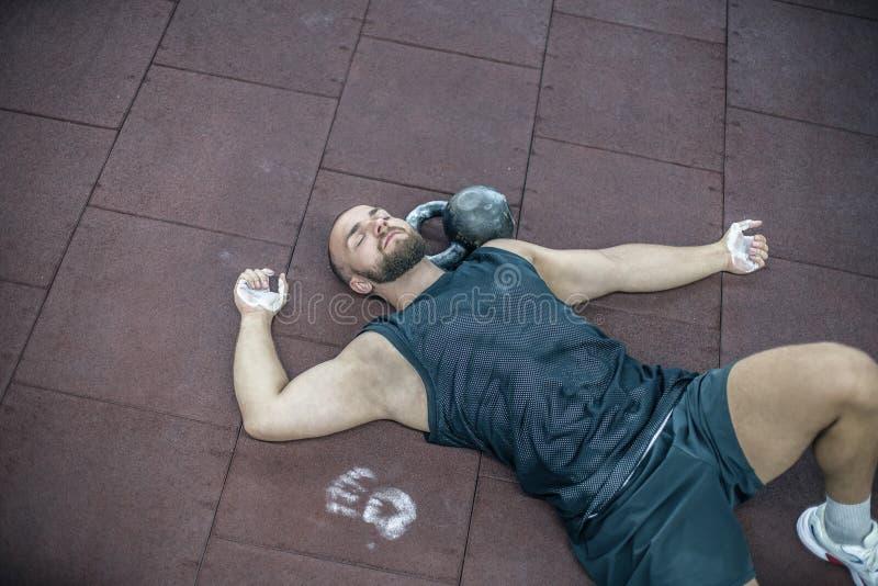 Giovane stanco che si trova sul pavimento e che si rilassa nella palestra dopo la formazione Maschio che si rilassa dopo la sessi immagine stock libera da diritti