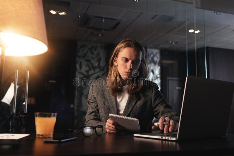 Giovane stanco con capelli lunghi che funzionano all'ufficio del sottotetto di notte Lavoro del collega in studio coworking moder fotografia stock libera da diritti