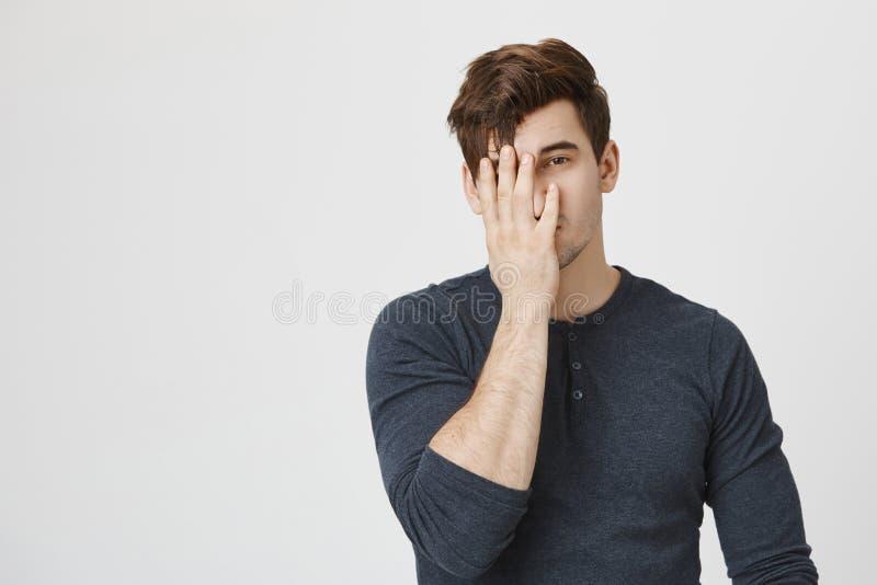 Giovane stanco ed esaurito nel fronte mezzo della copertura casuale del pullover con la mano mentre stando contro il fondo grigio immagine stock