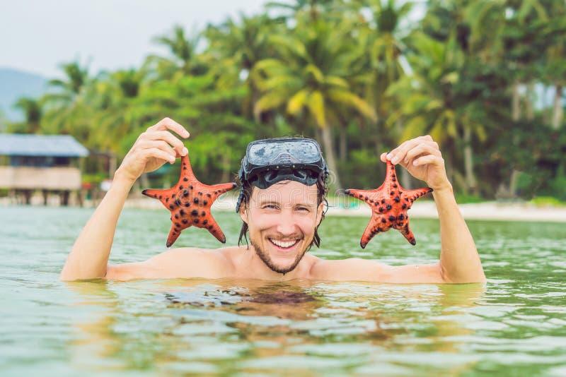 Giovane stella di mare felice della tenuta del subaqueo, sorridere, esaminante macchina fotografica immagini stock