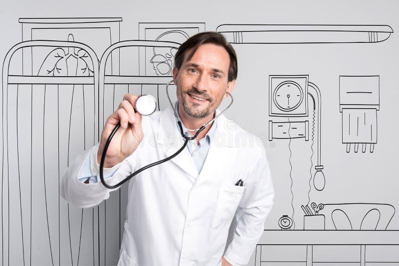 Giovane stetoscopio felice e sorridere della tenuta di medico immagini stock libere da diritti