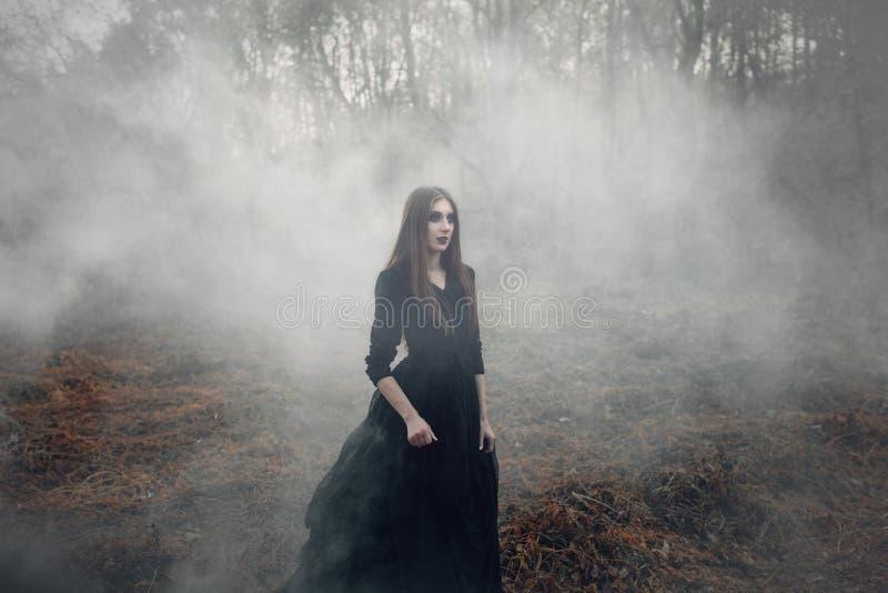 Giovane strega attraente che cammina sul campo in fumo nero pesante immagini stock libere da diritti