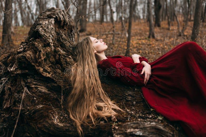 Giovane strega nella foresta di autunno