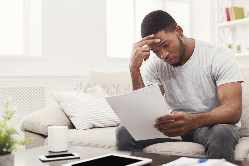 Giovane studente afroamericano stanco che legge a casa fotografia stock