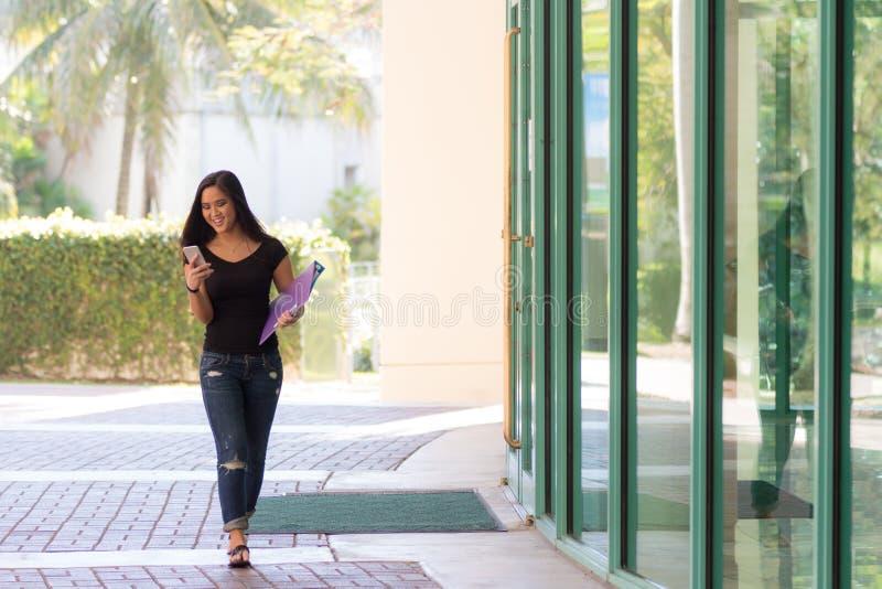 Giovane studente asiatico attraente che scrive un messaggio a macchina sul suo Smart-pho immagini stock libere da diritti