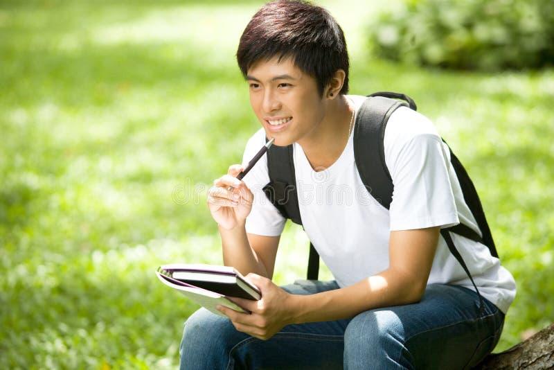 Giovane studente asiatico bello con i libri ed il sorriso in all'aperto fotografia stock libera da diritti