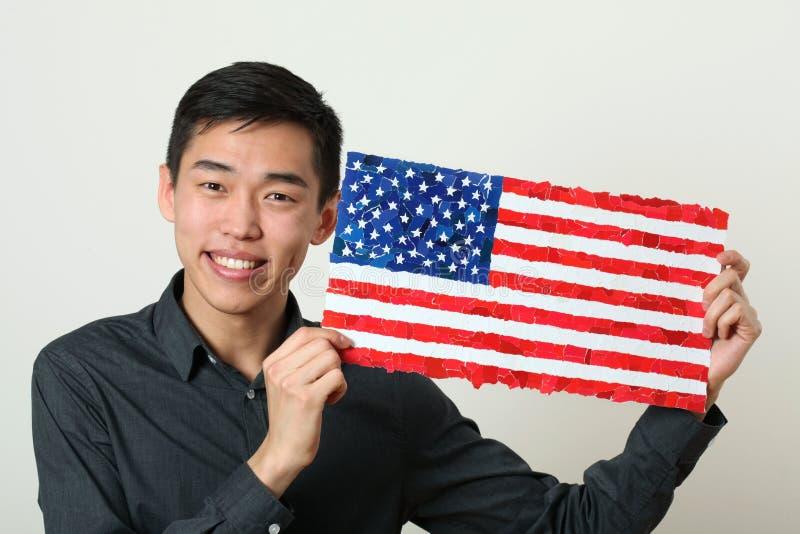 Giovane studente asiatico che mostra la bandiera nazionale degli Stati Uniti immagine stock libera da diritti