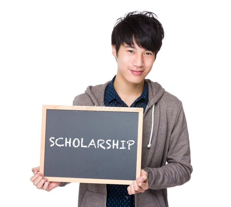 Giovane studente asiatico con la lavagna che mostra una borsa di studio di parola fotografia stock libera da diritti