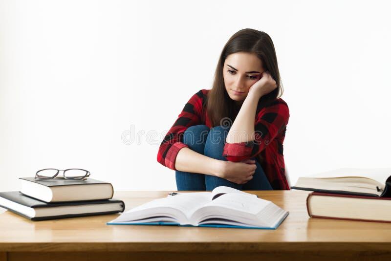 Giovane studente con l'espressione disperata che si siede al suo scrittorio immagini stock