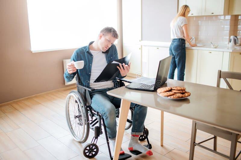 Giovane studente concentrato serio con inclusivit? ed handicappati Studiando e parlare sul telefono Tazza di caff? della tenuta immagini stock libere da diritti