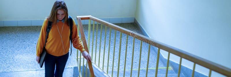 Giovane studente di college femminile solo depresso che cammina giù le scale alla sua scuola, guardante giù Istruzione, oppriment immagine stock libera da diritti
