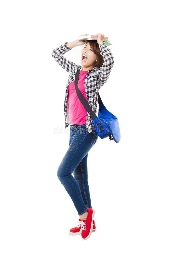 Giovane studente felice con i libri ed isolato su bianco fotografia stock