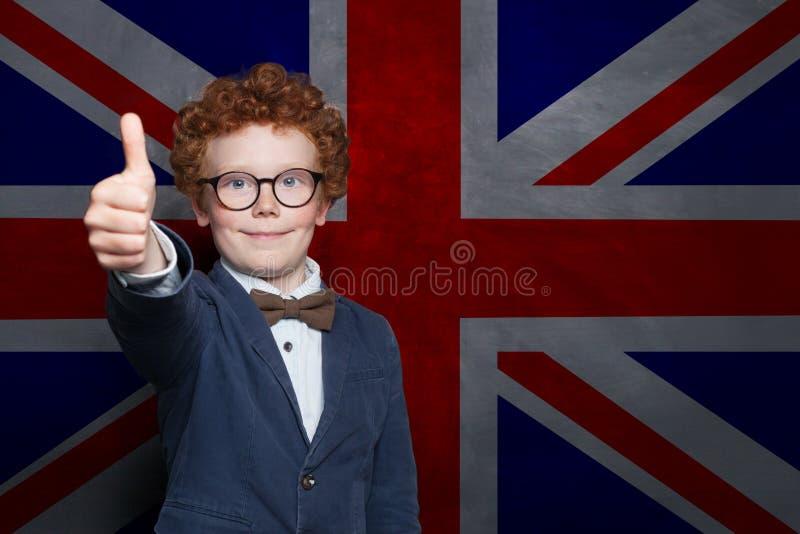 Giovane studente felice del ragazzo sui precedenti BRITANNICI della bandiera Impari la lingua inglese fotografia stock libera da diritti
