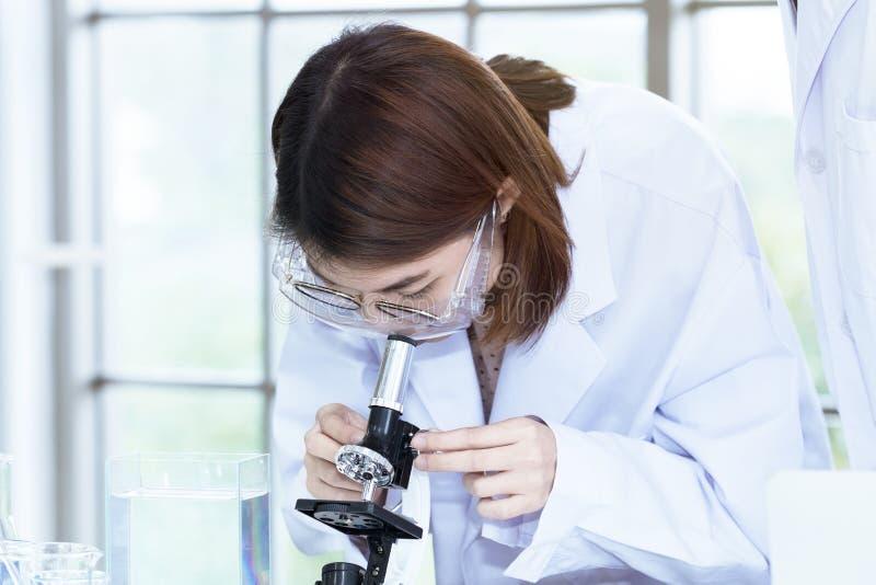 Giovane studente femminile dello scienziato che guarda tramite un microscopio immagine stock