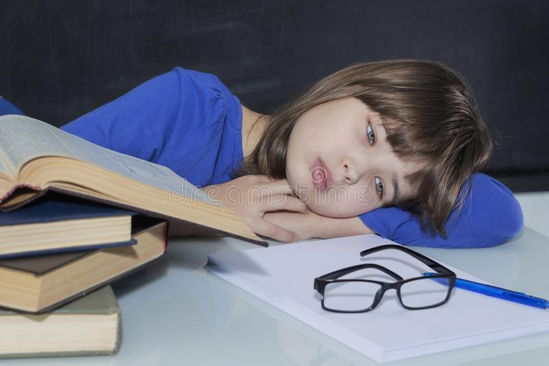 Giovane studente laborioso splendido stanco fra i suoi libri mentre studiando fotografie stock