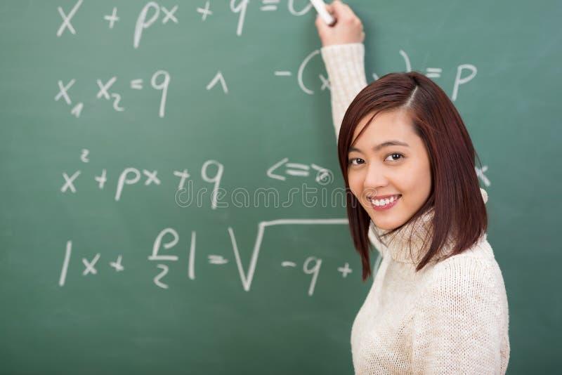 Giovane studente o insegnante sorridente che fa i per la matematica immagine stock libera da diritti