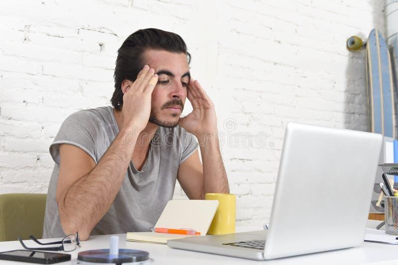 Giovane studente o uomo d'affari preoccupato allo sforzo ed all'emicrania di sofferenza del computer immagine stock libera da diritti